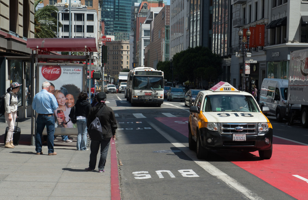 Taxi and Muni bus driving. Pedestrians waiting at bus stop.