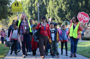 Children waiting to cross the street with volunteer crossing guard. Links to website.